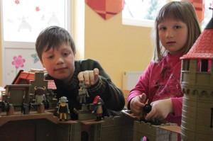 Jannik und Alina spielen zusammen mit Play Mobil. Ritter und Burgen sind schon aufgebaut.